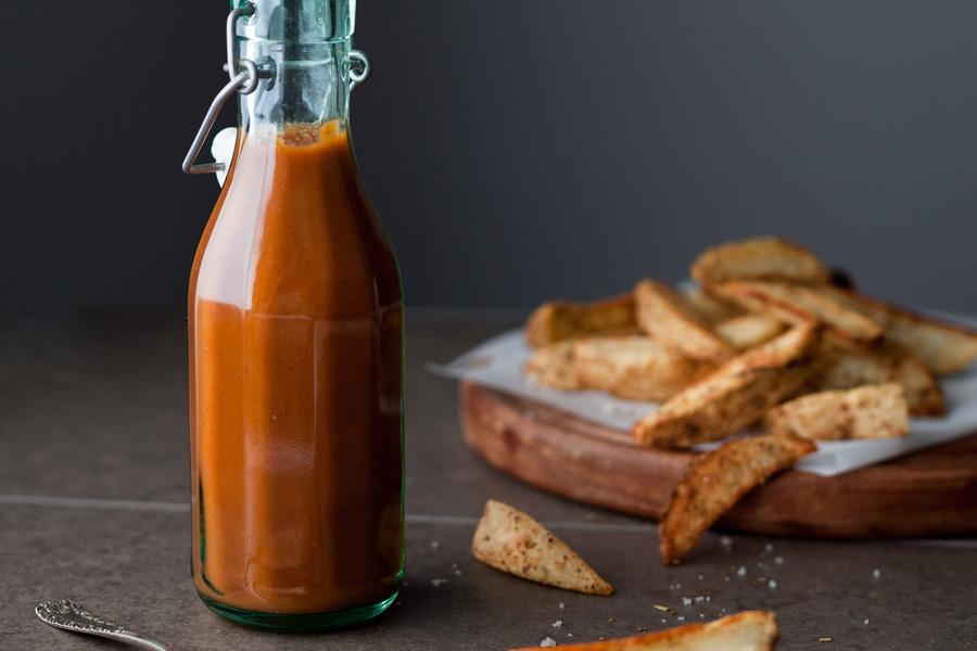 Una botella de cristal con ketchup casero con patatas al fondo.