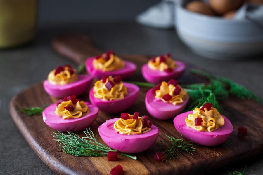 Huevos rosas rellenos sobre una tabla