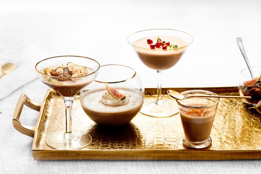 Pudin de chocolate en vasos y copas sobre una bandeja
