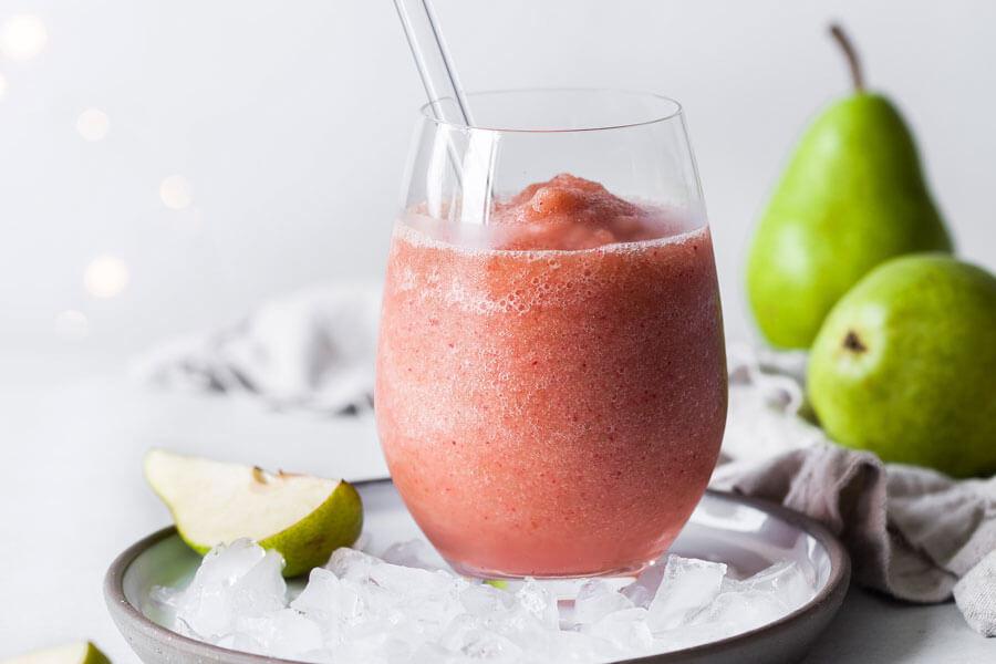 Smoothie de pera en un vaso de cristal con peras de fondo