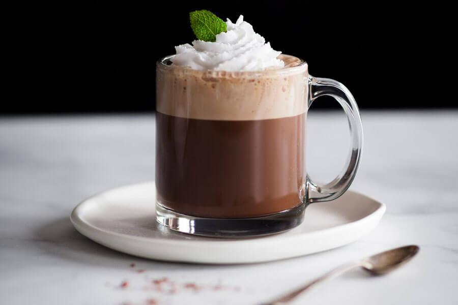 Cafe moka de menta en una taza de cristal decorado con nata