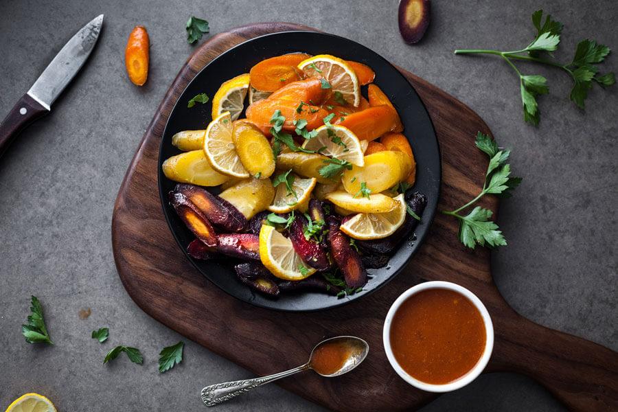 Vinagreta de salsa harissa en un bol junto a zanahorias horneadas