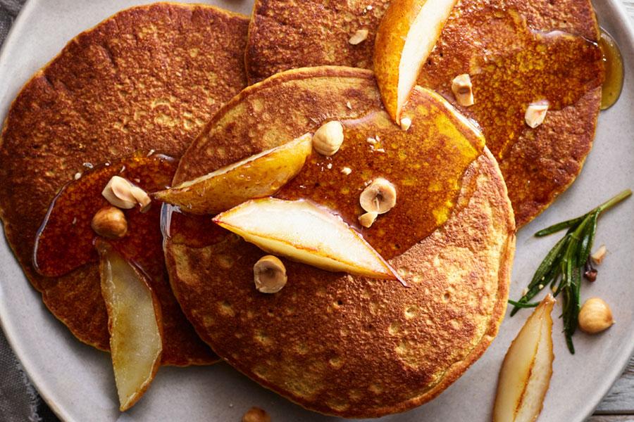 Tortitas con harina de almendra en un plato con manzana, sirope y avellanas partidas