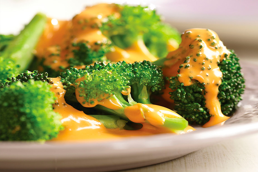 Salsa sin queso con sabor a queso sobre brócoli en un plato